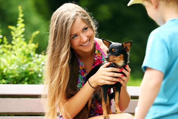 彼女の犬を示す若い女性 無料写真