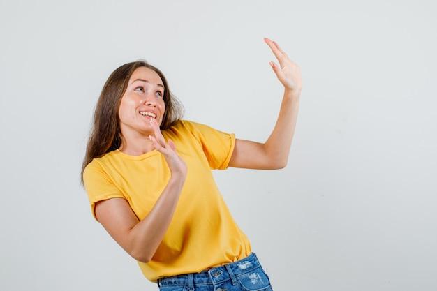 Молодая женщина в футболке, шортах вежливо показывает отказный жест и выглядит испуганной Бесплатные Фотографии