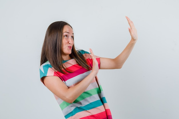 Young woman showing refusal gesture in t-shirt and looking scared , front view. Free Photo