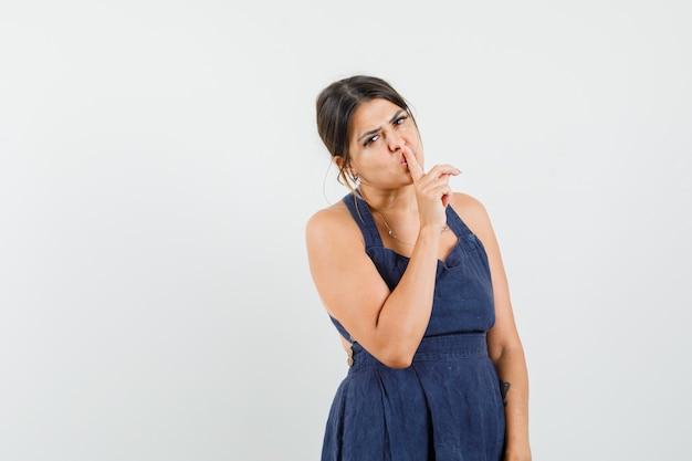 ドレスを着て沈黙のジェスチャーを示し、注意深く見ている若い女性 無料写真