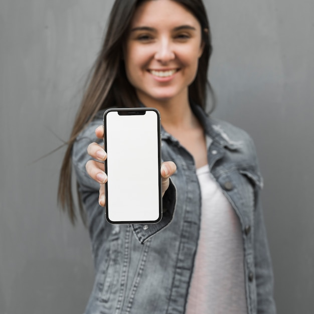 Young woman showing smartphone in hand Free Photo