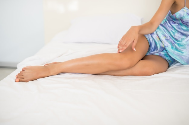 Young woman showing smooth silky skin legs after epilation on bed at home Free Photo