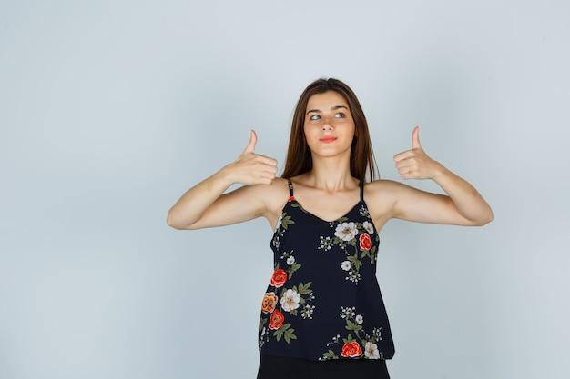 親指を立てて、花柄のトップスで横を向いて、かわいく見える若い女性 無料写真