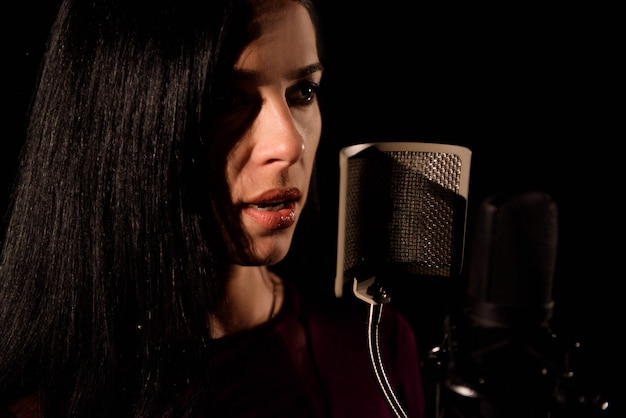 Young woman singer in front of microphone. Premium Photo