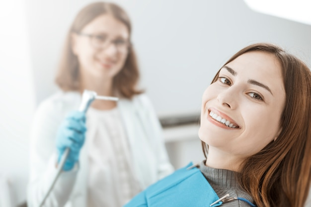 A young woman sits in a dental chair and smiles with white and healthy teeth Premium Photo