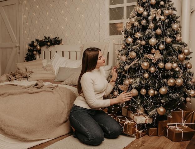 Молодая женщина сидит в белой рубашке для гольфа возле елки в спальне. Premium Фотографии
