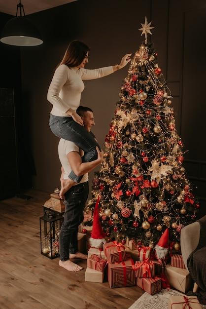Молодая женщина сидит на спине мужчины и украшает елку Premium Фотографии