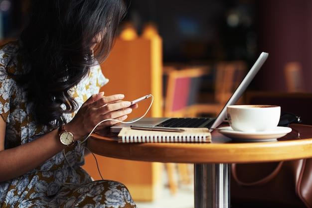 Молодая женщина, сидя за столом в кафе с ноутбуком и смартфоном Бесплатные Фотографии