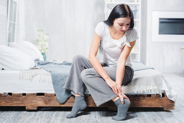 A young woman sitting on bed having pain in her ankle Free Photo