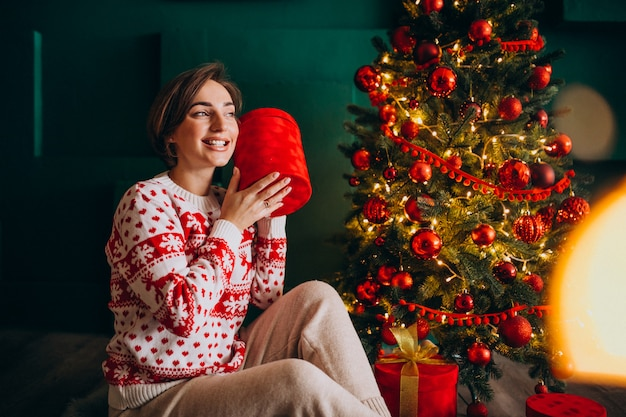 Young woman sitting by the christmas tree with red boxes Free Photo