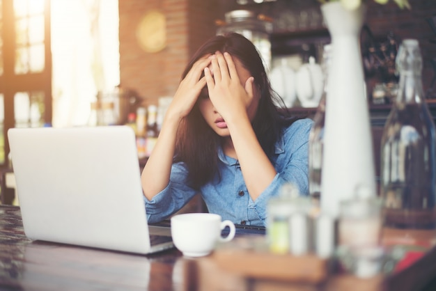 Young woman sitting in a cafe with her laptop, stressful for wor Free Photo