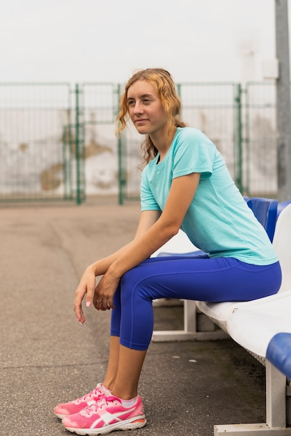 Young woman sitting on chair looking away Free Photo