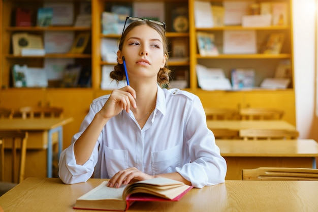 A young woman sitting at a desk in a white shirt Premium Photo