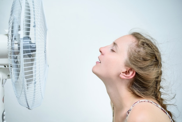 Young woman sitting under a fan with closed eyes from pleasure. summer heat. Premium Photo