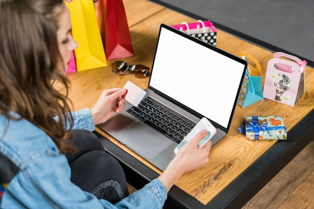 Young woman sitting in front of laptop with blank screen holding mobile phone and credit card in hand Free Photo