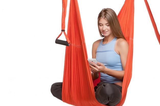 Молодая женщина сидит в гамаке для антигравитационной воздушной йоги Бесплатные Фотографии