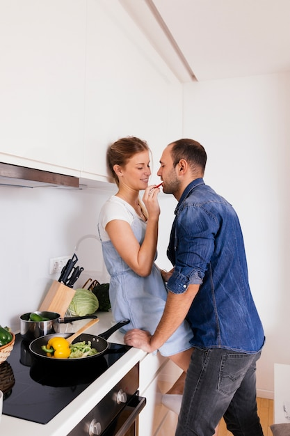 Young woman sitting on kitchen counter feeding salad to her husband