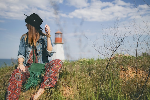 Young woman sitting in nature, lighthouse, bohemian outfit, denim jacket, black hat, smiling, happy, summer, stylish accessories Free Photo