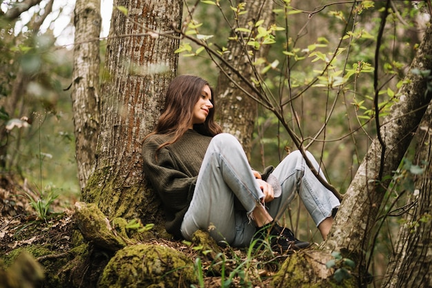 Young woman sitting in nature Free Photo