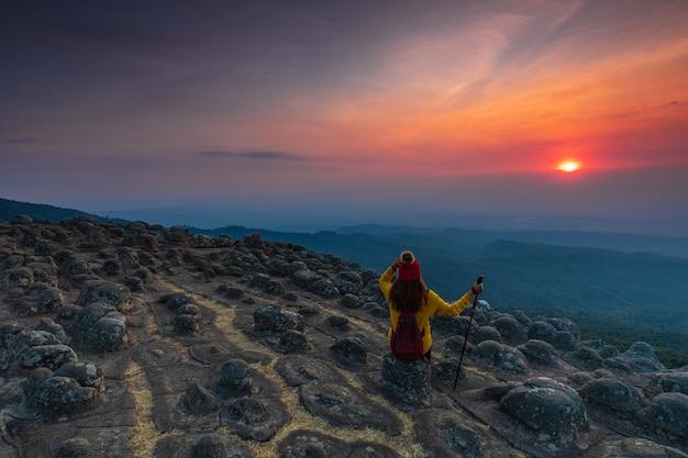 Молодая женщина сидит на скале в горах Premium Фотографии