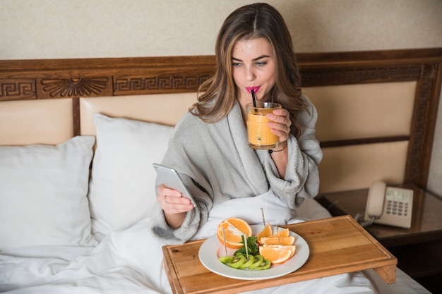 Young woman sitting on bed having nutritious breakfast looking at smart phone Free Photo
