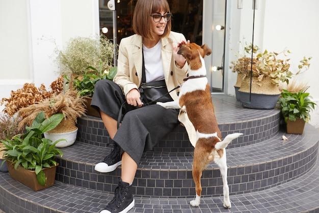 階段に座っている若い女性は犬の綱をつけており、近くには素敵なペットのジャックラッセルテリアがいます 無料写真
