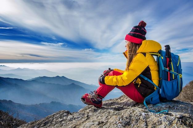 高山の丘の上に座っている若い女性 無料写真