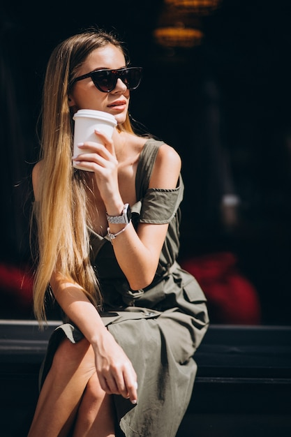 Young woman sitting outside the cafe drinking coffee Free Photo