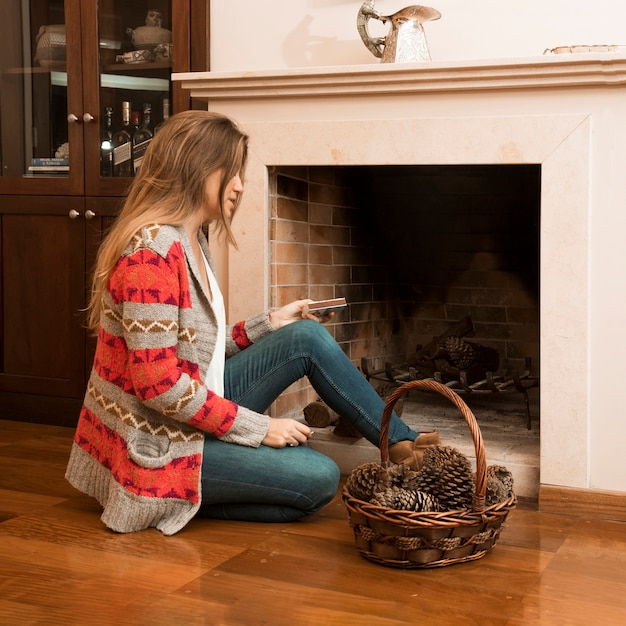 Young woman sitting outside the fireplace with matchbox and pinecone basket Free Photo