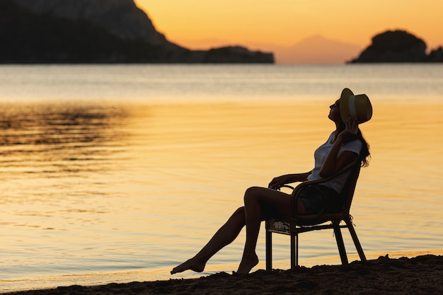Young woman sitting on seat on sunset on the shore of a lake Free Photo