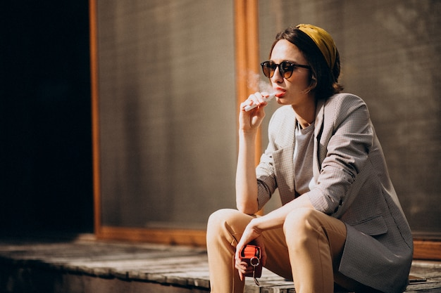 Young woman sitting and smoking ecigarette Free Photo
