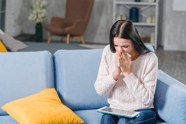 Young woman sitting on sofa blowing her nose looking at digital tablet Free Photo