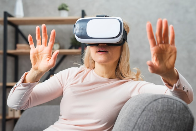 Young woman sitting on sofa experience with virtual reality Free Photo