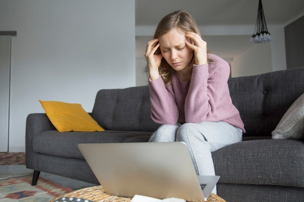 Young woman sitting on sofa with closed eyes, having headache Free Photo