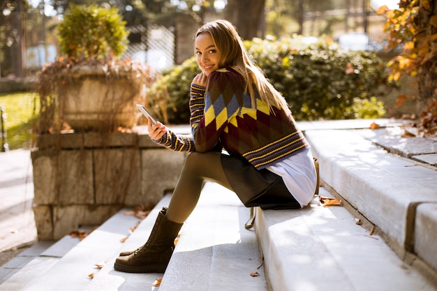 Young woman sitting on a stairs with mobile phone in autumn park Premium Photo