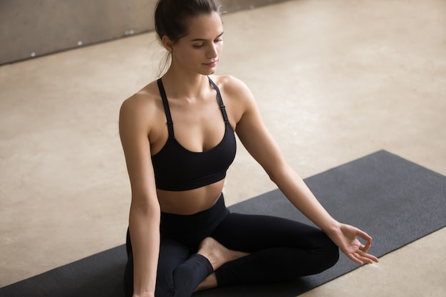Young woman sitting in sukhasana pose with mudra, grey studio Free Photo