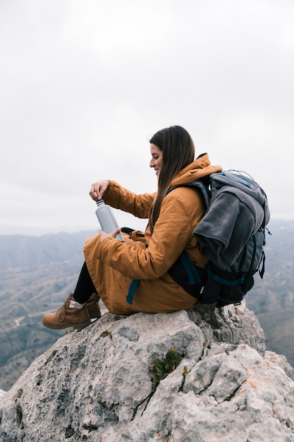 Young woman sitting on the top of mountain with her backpack holding the bottle of water Free Photo