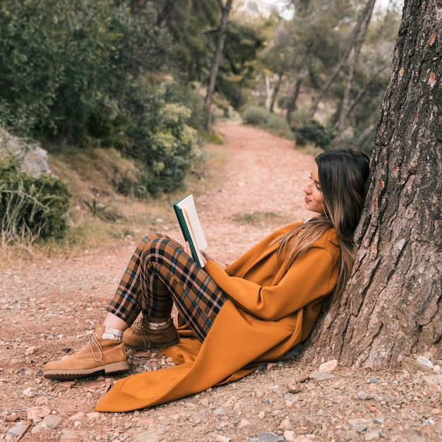 Young woman sitting under the tree on the way reading book Free Photo