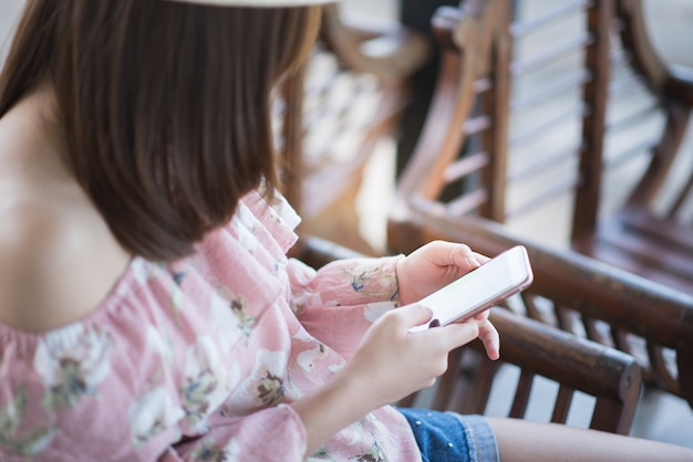 Young woman sitting and using mobile phone Premium Photo