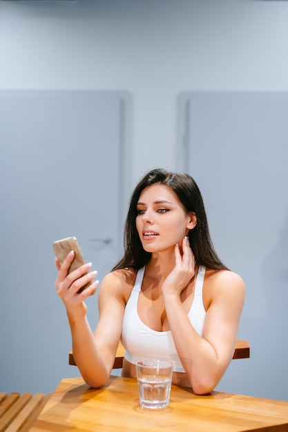 Young woman sitting and using smartphone after training Free Photo