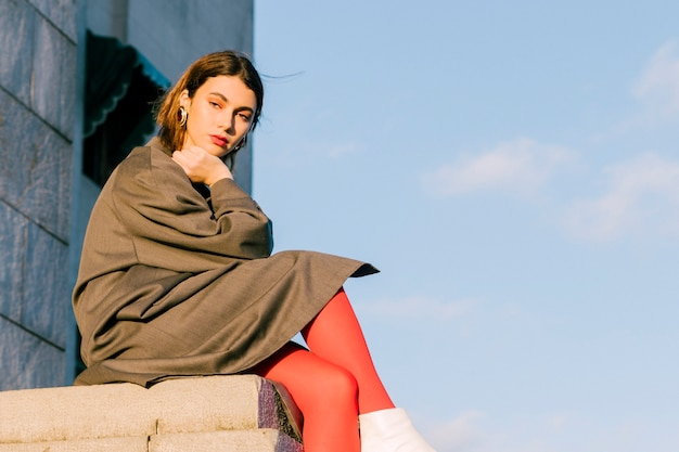 Young woman sitting on wall with her crossed legs against blue sky Free Photo