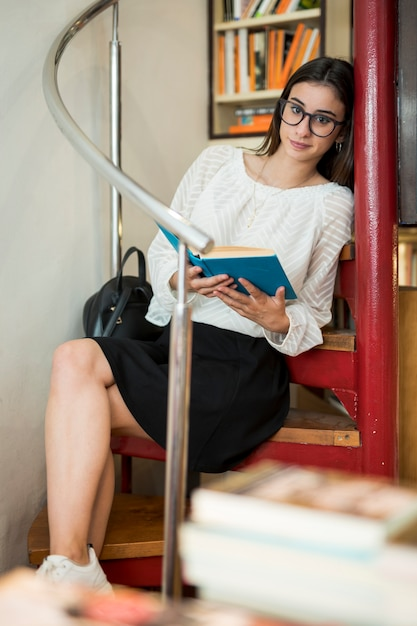 Young woman sitting with book looking at camera Free Photo