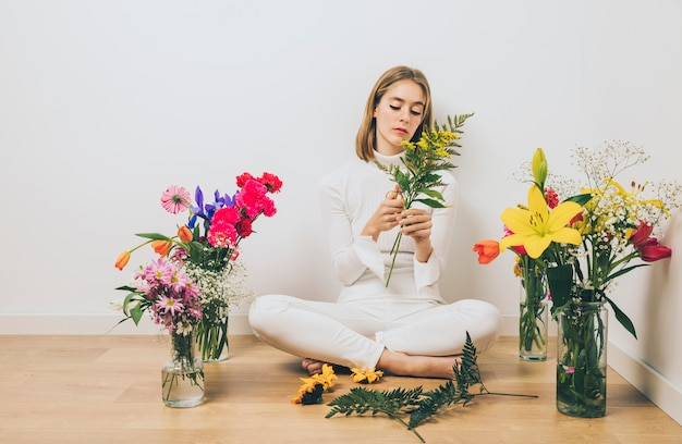 Young woman sitting with plants on floor Free Photo