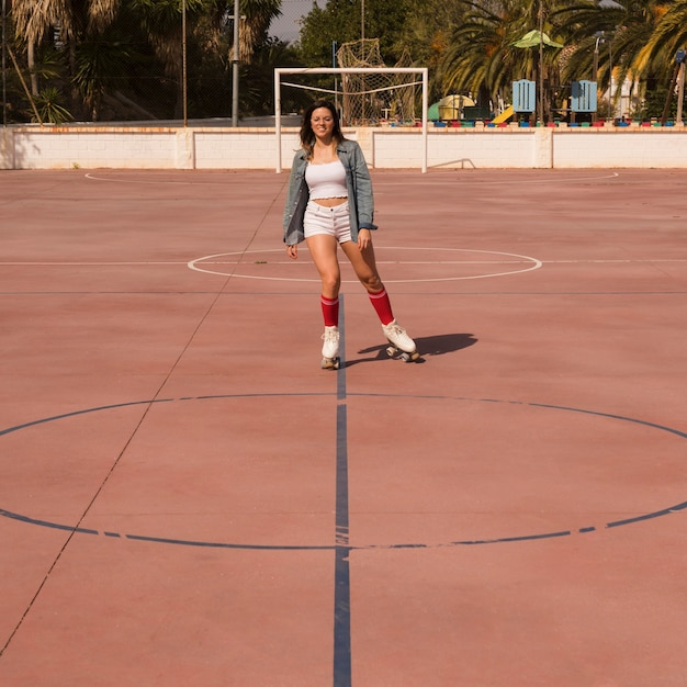 Young woman skating on the outdoor football court Free Photo