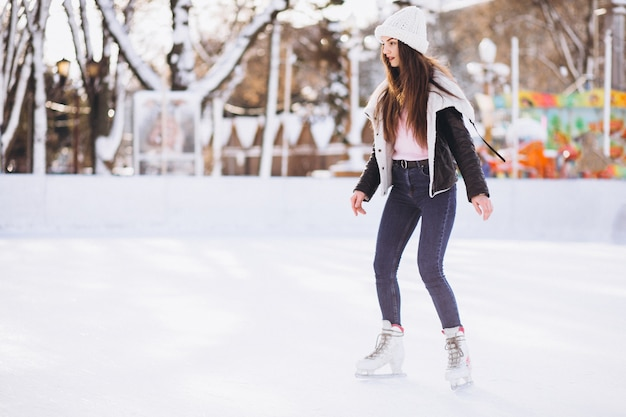 Young woman skating on a rink in a city center Free Photo