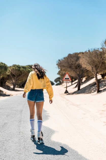 Young woman skating on roller skates on paved way Free Photo
