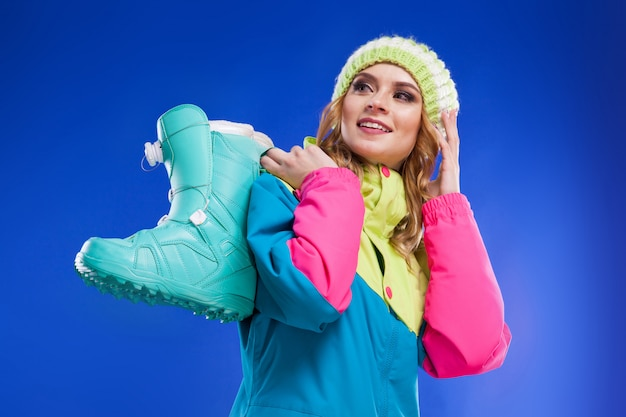Young woman in ski suit hold blue ski boots Premium Photo