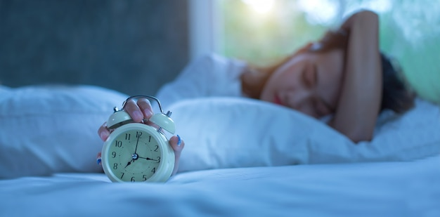 Young woman sleeping in bed with alarm at night Premium Photo