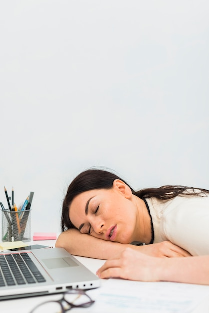 Young woman sleeping at table with laptop Free Photo