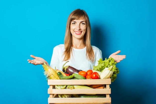 若い女性は笑顔し、青の新鮮な野菜のボックスを保持しています。豊作コンセプト、天然物 Premium写真